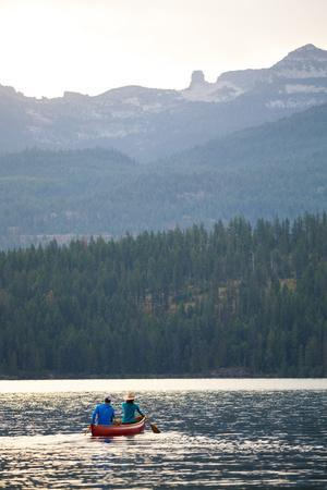 Man & Woman Paddle A Canoe While Shilo The Dog Enjoys The Ride At Sunrise On Priest Lake In N Idaho
