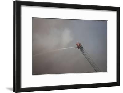 A Firefighter Battles a Fire from the Top of a Ladder Truck