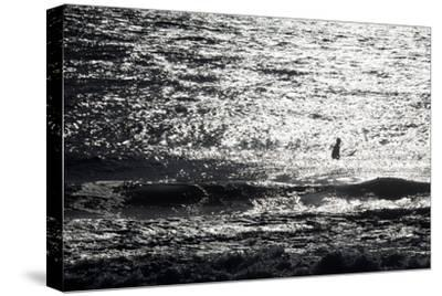 A Surfer Sits Alone Out in the Waves