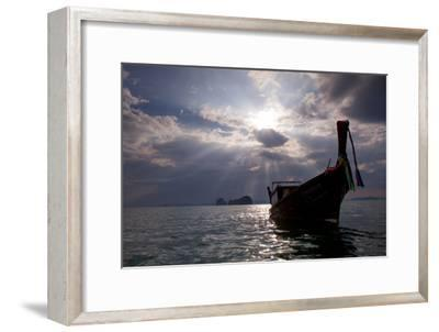 Andaman Sea: A Man Leans Off of a Long Tail Boat in the Andaman Sea under Rays of Light