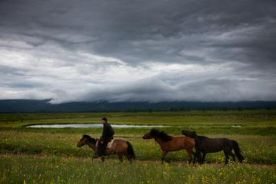 Mongolia: A Horseman Rides across the Mongolian Steppe with Horses in Tow