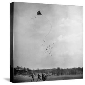 Children Playing with Kite That Releases Toys While in the Air by Bernard Hoffman