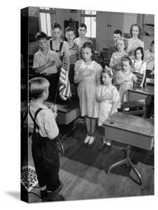 Children Reciting the Pledge of Allegiance as a Boy Holds the Us Flag in their Classroom by Bernard Hoffman