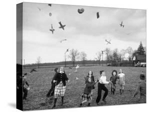 Children Trying to Catch Toys That Were Released by a Kite in the Air by Bernard Hoffman