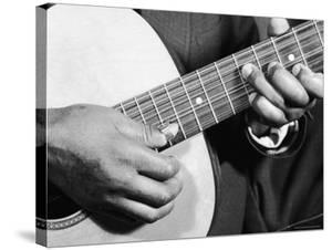 Close Up Shot of Musician Leadbelly, aka Huddie Ledbetter's Hands While Playing Acoustic Guitar by Bernard Hoffman