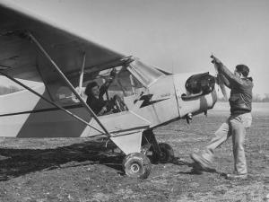 Marie Goerke Sitting in the Plane While the Instructor Kenny Garofalo Stops the Propellor by Bernard Hoffman