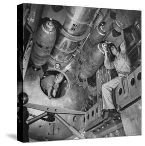 Ordnance Man Inserting Fuse Into 500 Lb. Demolition Bomb in Bomb Bay of B-29 by Bernard Hoffman