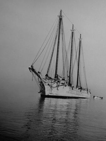 Three-Masted Schooner, Sails Furled, on the Water with a Dinghy in Tow by Bernard Hoffman