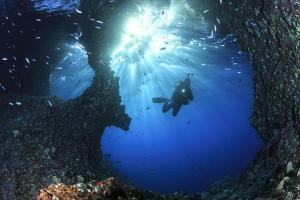 Scuba Diver Swimming through an Arch by Bernard Radvaner