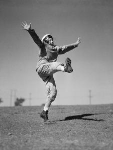 Boy Kicking a Football by Bettmann