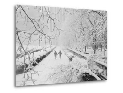 Couple Walking Through Park in Snow