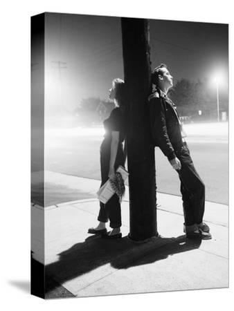 Teenagers Leaning on Utility Pole