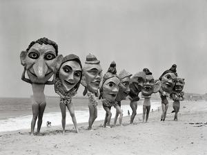 Women Holding Giant Masks by Bettmann