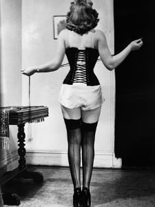 Young Woman Lacing Her Corset by Bettmann