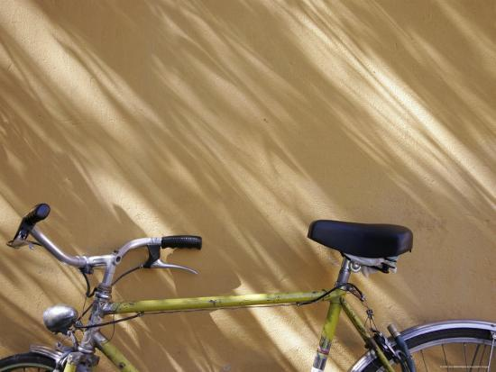 Bicycle Leaning against a Shadowed Yellow Wall, Parma, Italy-Gina Martin-Photographic Print