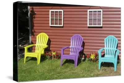 Canada, Peggy's Cove, Nova Scotia, Barn with Colorful Adirondack Chairs with Flowers