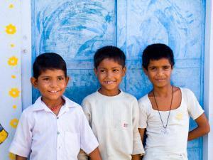 Children Against Blue Wall in Jaipur, Rajasthan, India by Bill Bachmann