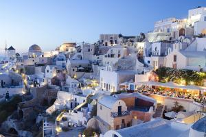 Greece, Santorini, Oia. white buildings and steep mountains at sunset. by Bill Bachmann