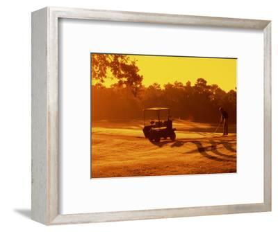 Man and Golf Cart Silhouetted at Sunset