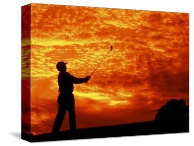 Man Swinging Golf Club at Sunset