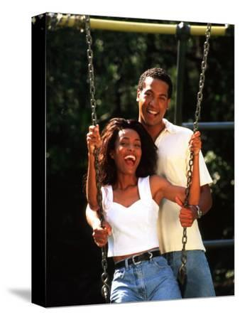 Middle-aged African-American Couple Playing on Swings in the Park