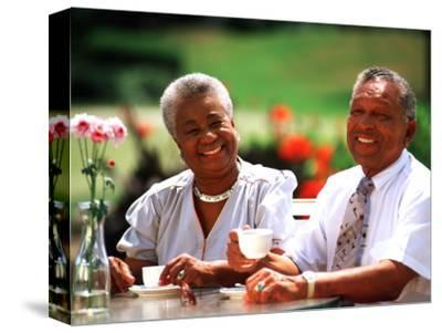 Retired African-American Couple Eating Together at Outdoor Cafe