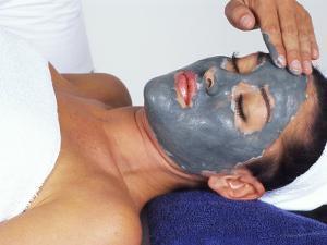 Young Woman Receiving Facial Treatment by Bill Bachmann