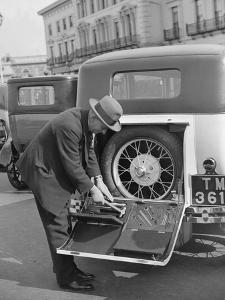 A driver opening the fitted toolkit of his Ford Model A at the Southport Rally, 1928 by Bill Brunell