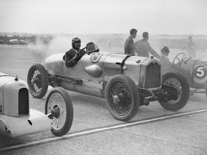 Riley, Buick and Bugatti on the start line at a Surbiton Motor Club race meeting, Brooklands, 1928 by Bill Brunell