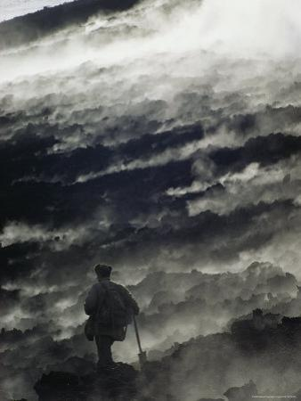 A Man Walking Across Steaming Ground Near an Active Volcano