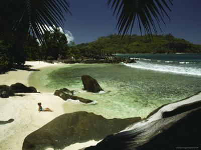 A Woman Sitting on an Idyllic Tropical Beach