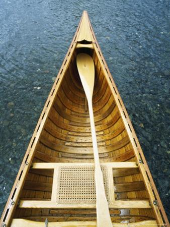 The Bow and Oar of a Handmade Wooden Canoe Resting in Water by Bill Curtsinger