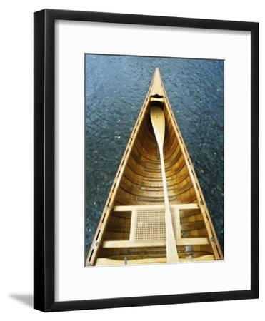 The Bow and Oar of a Handmade Wooden Canoe Resting in Water