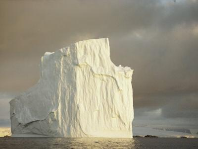 Twilight View of a Large Iceberg Under a Cloudy Sky