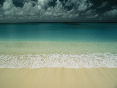 Wave Rolls over a Tranquil Beach in the Marshall Islands by Bill Curtsinger