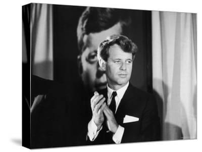 Robert F. Kennedy Campaigning in Front of Poster Portrait of His Brother President John F. Kennedy
