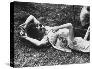 Young Couple Relaxing During Woodstock Music Festival by Bill Eppridge