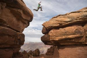 A Hiker Jumps from One Cliff to Another on the North Rim of Grand Canyon National Park by Bill Hatcher