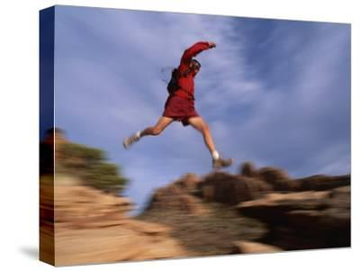 A Runner Leaps Across Rocks in Moab, Utah