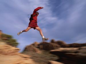 A Runner Leaps Across Rocks in Moab, Utah by Bill Hatcher