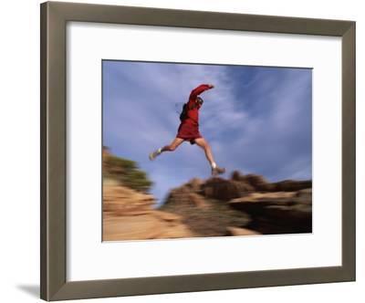 A Runner Leaps Across Rocks in Moab, Utah