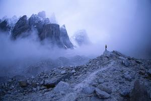 An expedition member surveys the mist-shrouded peaks surrounding Nameless Tower . by Bill Hatcher