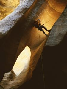 Man Rappelling Down a Canyon in Zion National Park by Bill Hatcher
