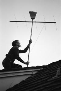 1967: Man Using a Broom to Improve the Antennae Reception During the Broadcast of Super Bowl I by Bill Ray