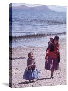 Mother and Two Children Holding Ball of Yarn, Andean Highlands of Bolivia by Bill Ray
