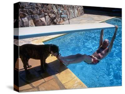 Sen. Barry Goldwater Hanging Underneath Diving Board in Swimming Pool as Dog Licks His Toes