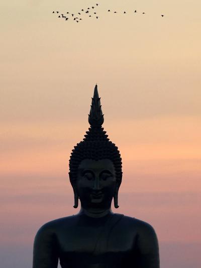 Birds Fly Past the Head of a Giant Buddha at Wat Muang-Barbara Walton-Photographic Print