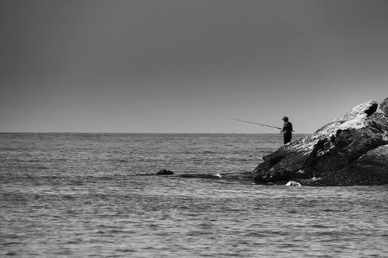 Black and White shot of a lone fisherman on rocks at the beach--Photo