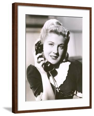 Blonde Woman Holding Telephone Receiver--Framed Photo