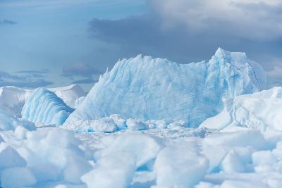 Blue Iceberg Floats Amidst Sea Ice in Fournier Bay, Antarctica-Jeff Mauritzen-Photographic Print